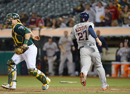 Jose Altuve scores the go-ahead run for the Astros, who win the first two games of the series against the A's. (USATSI)