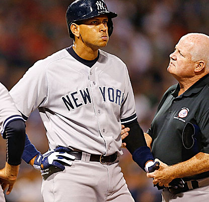 A trainer tends to Alex Rodriguez after the Yankees slugger was beaned by a pitch in the second inning. (Getty Images)
