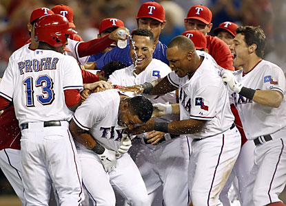 The Rangers mob Elvis Andrus, who delivers the winning RBI to help Texas complete its 40th comeback of the season. (USATSI)