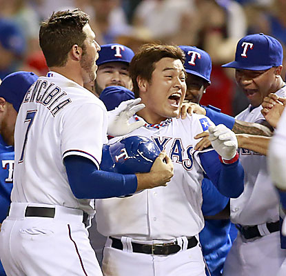 Shin-Soo Choo gets mobbed by teammates after he draws a walk-off walk to secure Texas' second straight ninth-inning comeback. (USATSI)
