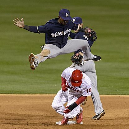 Milwaukee shortstop Jean Segura leaps over Philadelphia's Tony Gwynn Jr. after making a force play in the sixth inning.  (USATSI)