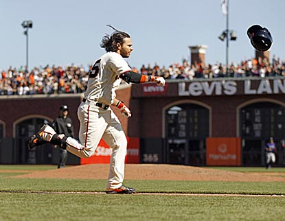 Brandon Crawford tosses his helmet before he completes his tour of the bases following his winning home run.  (USATSI)