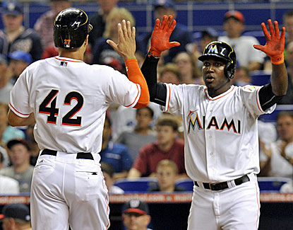 Giancarlo Stanton (left) celebrates with Marcell Ozuna after both score in the second inning against the Nationals. (USATSI)