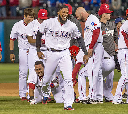 The Rangers celebrate after Leonys Martin (ground) drives in the winning run to complete the ninth-inning rally. (USATSI)