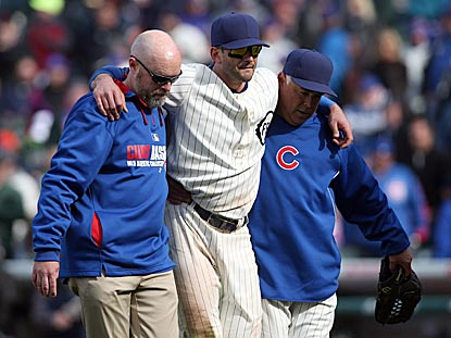 How apropos: Justin Ruggiano is helped off the field after injuring himself while failing to catch the hit that beats the Cubs. (USATSI)