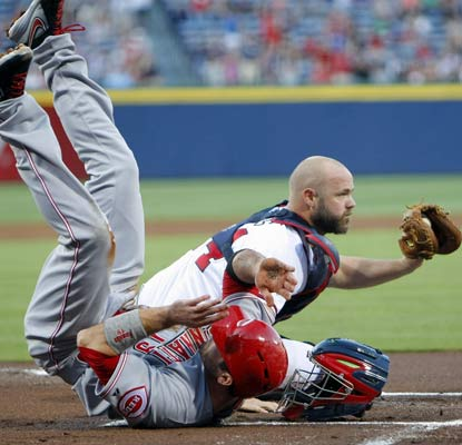 Evan Gattis tags out Joey Votto at home plate on a throw from Jason Heyward in the first inning.  (USATSI)