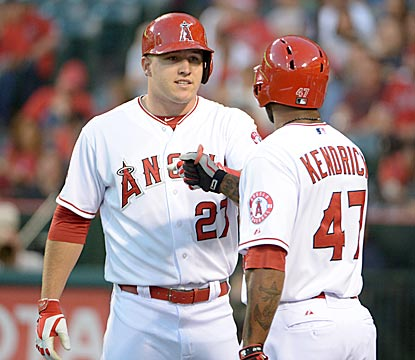 Mike Trout, here celebrating scoring a run in the first inning with Howie Kendrick, later drives in the winning run.  (USATSI)