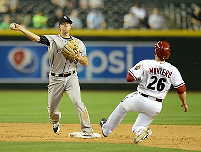 Despite Miguel Montero's attempt to break it up, Colorado's DJ LeMahieu turns a double play in the seventh inning.  (Getty Images)