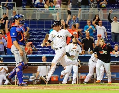 Christian Yelich scoots home to score the winning run as the Marlins dugout empties to begin the celebration.  (USATSI)