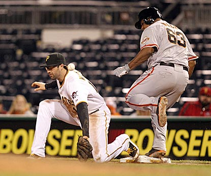 Neil Walker can't scoop out a low throw on Jean Machi's sacrifice bunt, which allows Hunter Pence to score the deciding run.  (USATSI)
