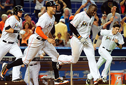 The Marlins celebrate after Marcell Ozuna's sacrifice fly in the ninth wins it and helps them finish their homestand 8-1. (USATSI)