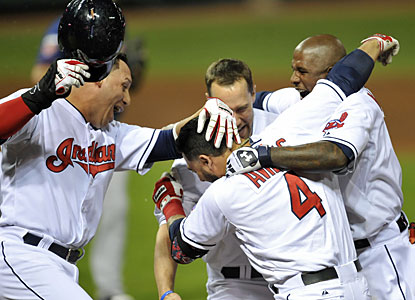 The Indians' Mike Aviles gets mobbed by teammates after he delivers the winning RBI single with two outs in the ninth. (USATSI)