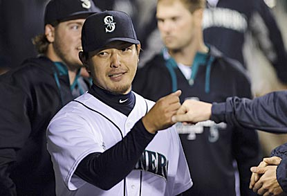 Hisashi Iwakuma receives congratulations at the end of his stellar outing: four hits and no walks in eight shutout innings. (USATSI)