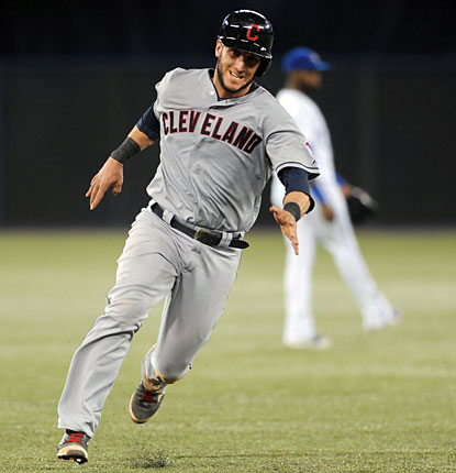 Yan Gomes runs past Blue Jays shortstop Jose Reyes as he scores the Indians' sixth run. (USATSI)