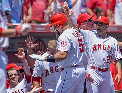Albert Pujols gets a hearty welcome after opening the scoring with a solo home run in the first inning.  (USATSI)