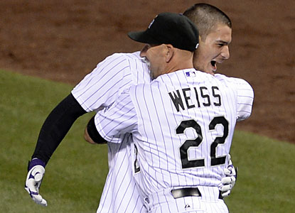 Rockies skipper Walt Weiss embraces game hero Nolan Arenado, who hits a walk-off, two-run double. (USATSI)