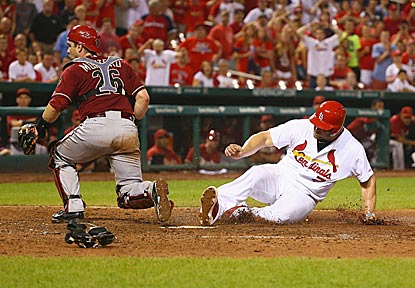 Matt Holliday slides in with the winning run as Arizona catcher Miguel Montero watches Chris Owings' errant throw sail by.  (Getty Images)
