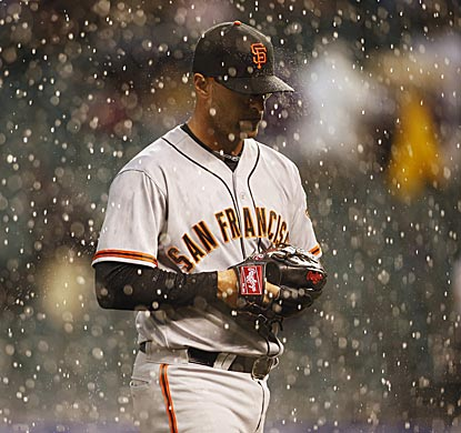 Giants reliever David Huff heads for the dugout as the second deluge of the day stops play in Denver.  (USATSI)