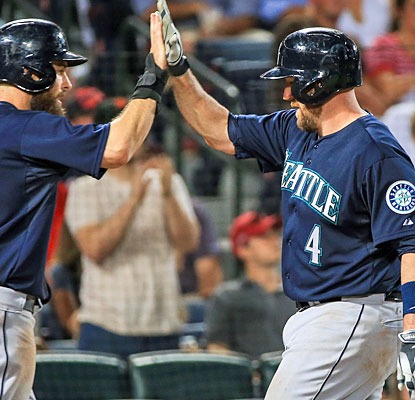 John Buck (right) finishes with three hits, including a two-run homer, to help his Mariners rally from four down. (USATSI)