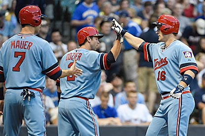 Twins teammates, wearing Minnesota's powder blue road uniforms from the mid-1980s, greet Josh Willingham after his home run.  (USATSI)