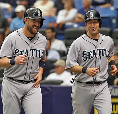 John Buck and Willie Bloomquist head back to the dugout after scoring on Robinson Cano's third-inning double.  (USATSI)