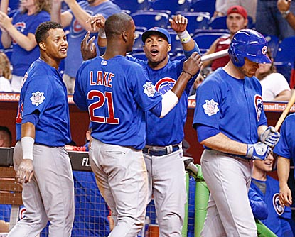 Junior Lake greets a happy Cubs dugout after Travis Wood drives him in with a pinch-hit double in the 13th.  (Getty Images)