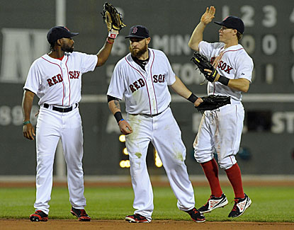 Jackie Bradley Jr., Jonny Gomes and Brock Holt, who scores two runs, celebrate the Boston win. (USATSI)