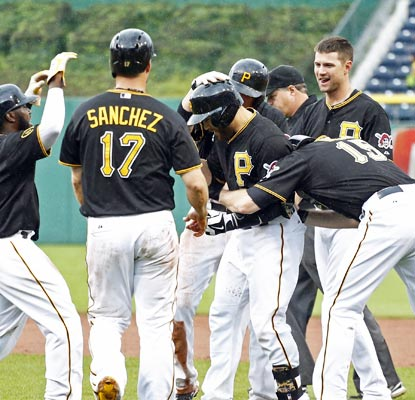 The Pirates mob Russell Martin after he draws a two-out, bases-loaded walk to end the game in the 12th inning.  (USATSI)