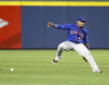 Juan Lagares mishandles Tommy La Stella's single in the eighth inning. The tying run scores on the play.  (Getty Images)