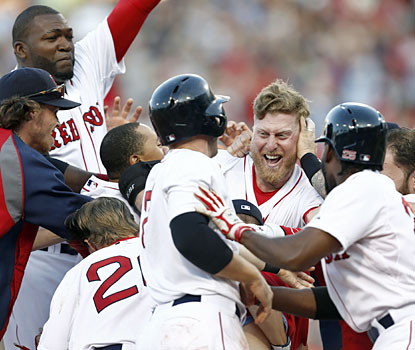 Mike Carp (center) produces the winning hit for the Red Sox, who battle back after blowing the lead in the ninth. (USATSI)