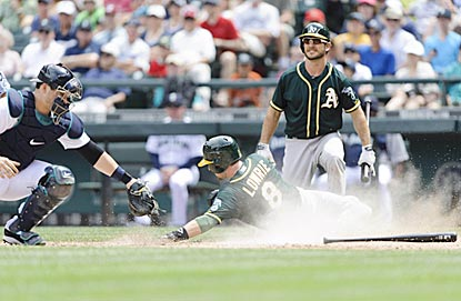 Oakland's Jed Lowrie slides past Seattle catcher Mike Zunino to score in the fifth inning and tie the game at 1.  (USATSI)