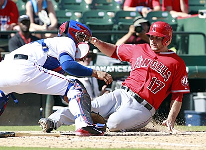 Chris Iannetta slides in ahead of Robinson Chirinos' tag in the eighth inning to boost the Angels' lead to 9-7.  (USATSI)