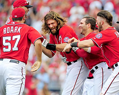Washington's Jayson Werth gets pummeled by his teammates after delivering the winning hit.  (USATSI)