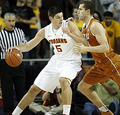 USC's Nikola Vucevic, left, is defended by Texas' Matt Hill on his way to scoring 24 points in the Trojans' upset win. (AP)