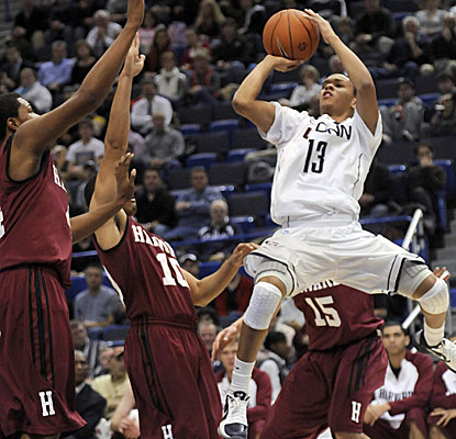 Connecticut's Shabazz Napier, right, takes a jump shot as two Harvard players defend. (AP)