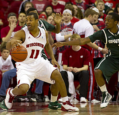 Badgers guard Jordan Taylor spins away from Michigan State defenders in Wisconsin's home win. (US Presswire)