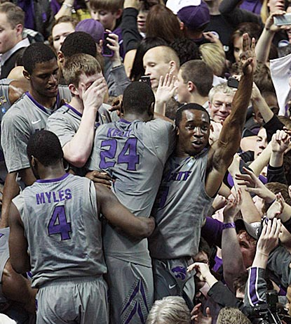 Martavious Irving (3), Juevol Myles (4) and Curtis Kelly (24) join the celebration after the Wildcats down the hated Jayhawks.  (AP)