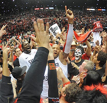 San Diego State players celebrate with fans after a win over CSU clilnches the Aztecs a share of the Mountain West title. (US Presswire)