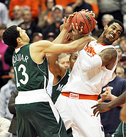 Syracuse's Fab Melo (right) fights for the ball, earning 11 points and a career-high nine rebounds against Manhattan. (AP)