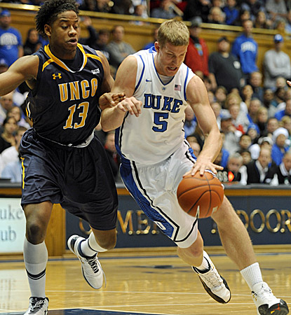 UNCG's Aloysius Henry (left) pressures Mason Plumlee, who scores 15 points and grabs 13 rebounds in Duke's 90-63 win. (AP)