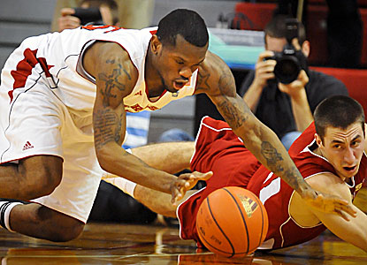 The Cornhuskers' Caleb Walker (left) battles Josh Gasser of the Badgers for a loose ball. (AP)