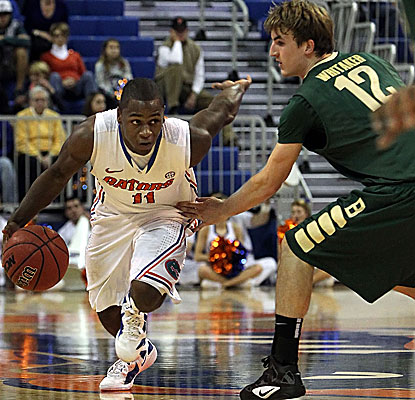 The Gators' Erving Walker (left) drives to the hoop for two of his game-high 23 points. (US Presswire)
