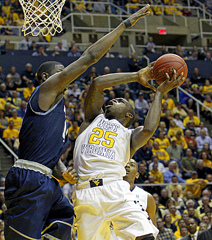 Georgetown's Henry Sims (left) fouls West Virginia's Darryl Bryant, who scores a game-high 25 points in the Mountaineers' win. (AP)