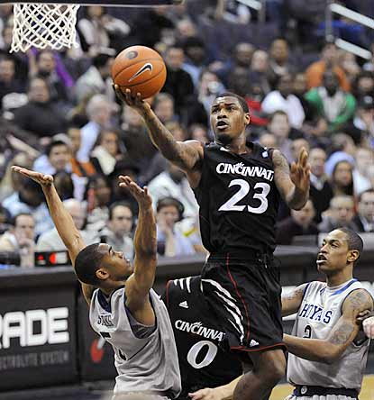 Cincinnati's Sean Kilpatrick (23) splits the defense of Georgetown's Markel Starks and Greg Whittington during the first half.  (AP)