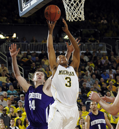 Trey Burke leads Michigan in a close one against Northwestern, scoring eight of his 19 points in overtime. (AP)