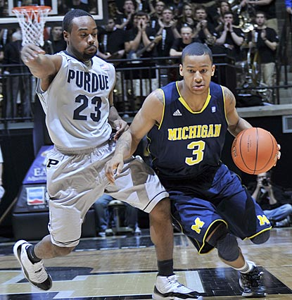 Trey Burke, shown dribbling against Purdue's Lewis Jackson, helps Michigan escape Mackey Arena with a victory.  (US Presswire)