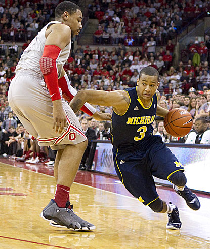 Michigan guard Trey Burke looks for driving room around Ohio State's Jared Sullinger, his former high school teammate.  (US Presswire)
