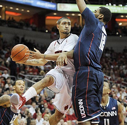 Louisville's Peyton Siva, who winds up with a game-high nine assists, looks for a teammate around UConn's Andre Drummond.  (US Presswire)