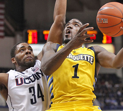 UConn big man Alex Oriakhi tries to deny Marquette's Darius Johnson-Odom, who finishes with 24 points.  (US Presswire)