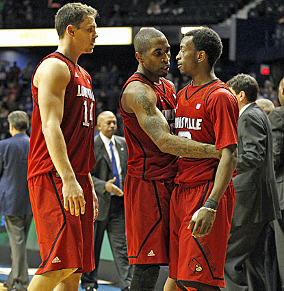 Louisville's Kyle Kuric (left) and Chris Smith celebrate with Russ Smith (right), who hits bacck-to-back baskets in overtime. (AP)
